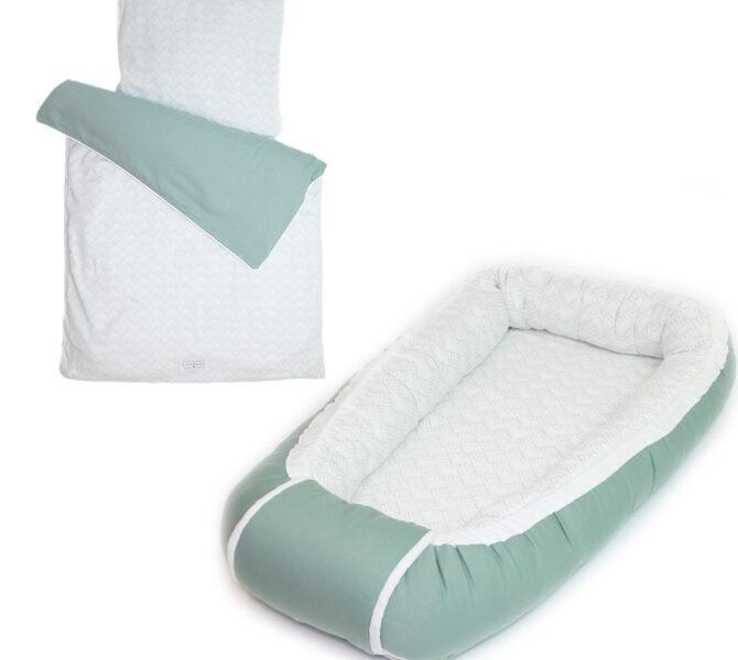 startpakke med grøn babynest og babysengetøj